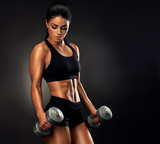 Beautiful fitness woman lifting dumbbells . Fitness sporty woman showing her well trained body . A beautiful girl