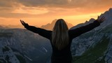 young woman raising arms  on top of a mountain sign of happiness success concept
