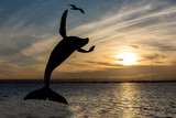 silhouette Humpback whale breaching statue at sunset