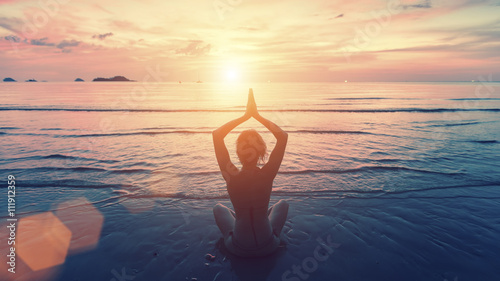 Poster Silhouette young woman practicing yoga on the sunset beach. Tranquility and concentration.
