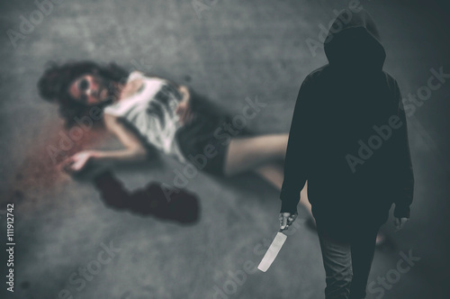 Poster Murderer hooded man ready to attack to kill his victim that is the woman to died on ground