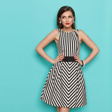 Fototapety Smiling elegant woman in black and white striped dress posing with hands on hip and looking away,