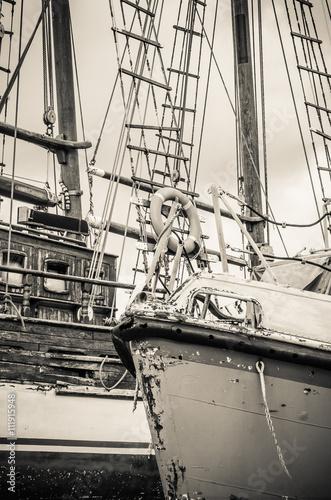 Old collapsing sailboats at the dock, close-up, sepia
