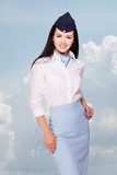 Charming Stewardess Dressed In blue Uniform. Sky With Clouds Background.