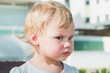 Portrait of serious cute Caucasian blond baby girl