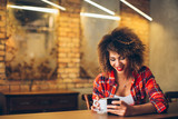 Fototapety Young woman at cafe drinking coffee and using mobile phone