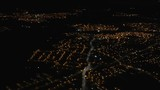 City lights at night from descending aircraft in flight before landing at Manchester airport, England, UK