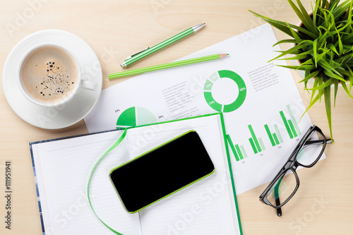 Fototapeta Office desk with charts, coffee, plant and phone