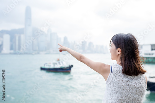 Woman finger point to the location in Hong Kong island Poster