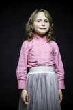 Beautiful little girl in a pink blouse and white skirt on a black textured background