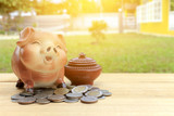 piggy bank and Thai money on wood background, over sunlight [blur and selective focus background]