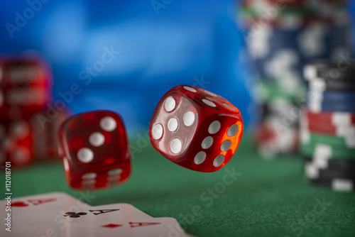 Two red dice rotates in the air, casino chips, cards on green felt плакат