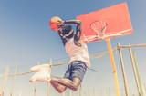 Basketball street player making a slam dunk outdoor