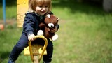 happy kid on a swing with a brown teddy bear