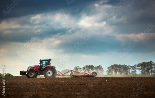 Farming tractor plowing and spraying on field Poster