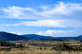 Rural landscape - paddock in foreground with mountains in the distance and an overcast, blue sky - 112066544