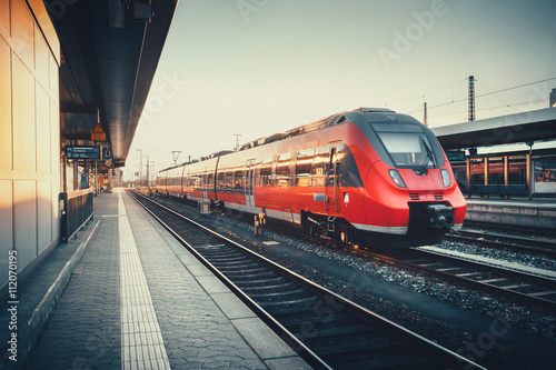 obraz PCV Beautiful railway station with modern red commuter train at colorful sunset in Nuremberg, Germany. Railroad with vintage toning