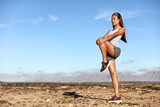 Standing Gluteus maximus leg stretches. Fitness woman doing stretch exercises workout stretching glutes muscles and hamstring as warm-up for cardio exercise. Trail running in summer outdoor nature.