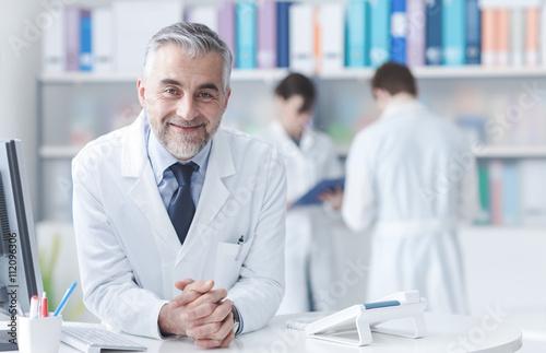 Confident doctor at the reception desk Plakat