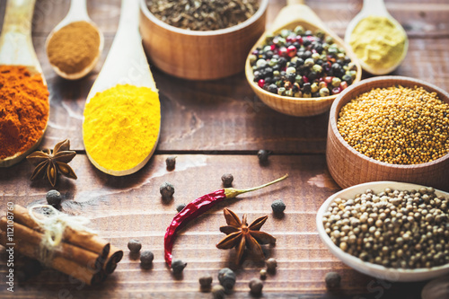 Poster Beautiful colorful spices in wooden spoons and bowls on an old wooden brown table