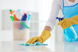Cropped image of housewife wiping table with spray