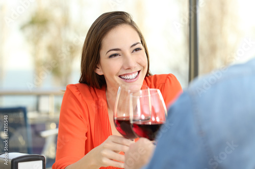 Woman toasting with wine in a date