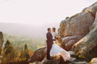 Quadro Portrait of romantic newlywed couple kiss in sunset lights on majestic mountain landscape with big rocks as backround