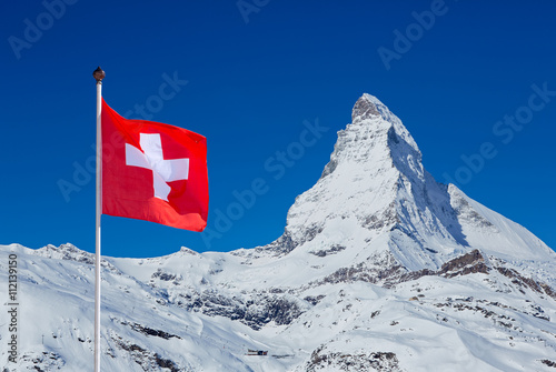 Poster Famous Matterhorn with flag of switzerland on blue sky