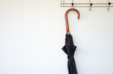 Umbrella of black color on a hook