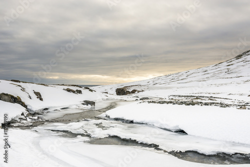 Fototapeta The frozen river in Iceland during sunset.