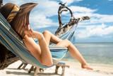 Frau im Urlaub am Strand entspannt in Hängematte am Meer - 112160385