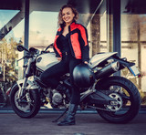 Blond female posing near motorcycle.
