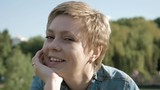 Pretty blond short hair woman with beautiful smile closeup portrait outdoor in a summer park. Sunny bright day and warm nice weather scene. 4K UHD video footage.