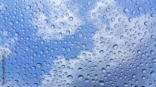 Raindrops on glass and blurred sky background