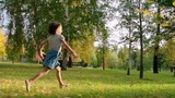 Little girl running through the lawn in park to her mother in slow motion, woman lifting her up and embracing with daughter