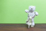 Teddy Bear toy Riding  bicycle on old wood  and green wall backg