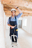 Builder smiling and holding hammer
