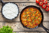 Traditional tikka masala chicken spicy meat Indian food with rice tomatoes and parsley in cast iron skillet on vintage wooden background - 112218970
