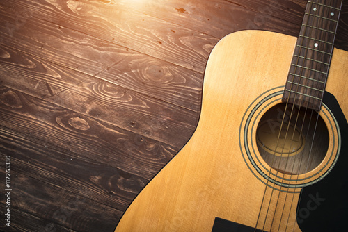 Acoustic guitar resting against a wooden background with copy sp - 112263330