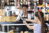 Saleswoman Accepting Payment Through Credit Card At Cheese Shop