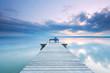 Frau sitzt entspannt auf einer Bank am Steg am See
