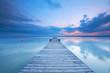 Holzsteg mit Bank am See zum Sonnenuntergang