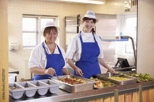 Deux femmes qui attendent de servir le déjeuner dans une cafétéria de l'écol Poster