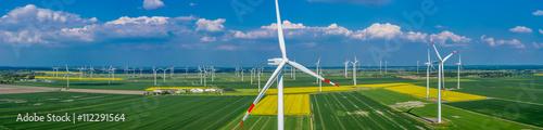 Fototapeta Panorama Luftbild und Nahaufnahme einer Windenergieanlage in einem Windpark mit Rapsfeld