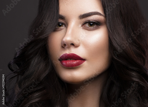 Zdjęcia Beautiful brunette model: curls, classic makeup and red lips