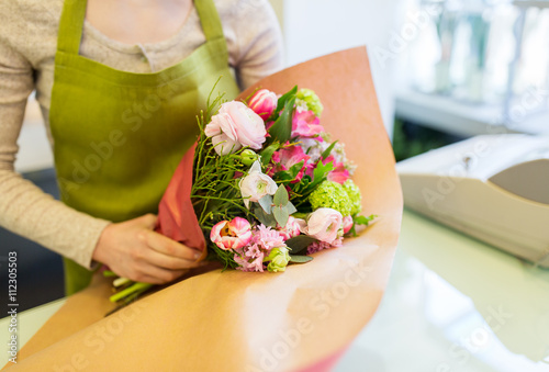close up of woman packing bunch at flower shop