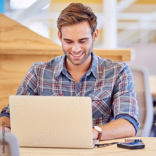 Poster Adult male student smiling at he types on his notebook