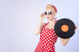 Pin-up girl in vintage dress holding a vinyl record