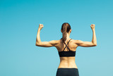Fototapety Girl power! Strong and confident woman flexing her muscle.