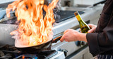 Fototapety Chef doing flambe to food in pan with alcohol